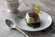 Sweet dessert dish with sugarwork and sauce on plate with spoon and cup. — Stock Photo