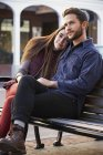 Young couple hugging on bench in urban street. — Stock Photo