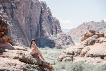 Young woman in white swimsuit sitting on rocks on canyon with cliffs and peaks. — Stock Photo