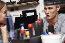 Young woman and man talking in technology lab with tools on table. — Stock Photo