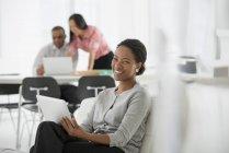Mulher segurando tablet digital enquanto sentado no sofá no escritório com colegas de trabalho usando laptop em segundo plano . — Fotografia de Stock
