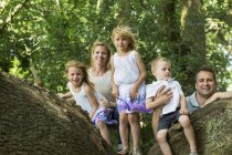 Family with three children posing on tree in park. — Stock Photo