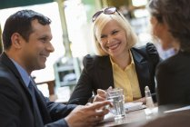 Man and women sitting in bar with drinks and chatting. — Stock Photo