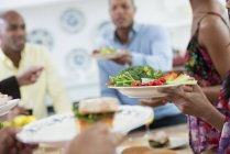 Cropped view of people handing plates of food across buffet table. — Stock Photo