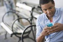Mann sitzt auf Bank in der Stadt und benutzt Smartphone. — Stockfoto