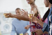 Cropped view of people holding wine glasses upon buffet table. — Stock Photo