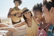 Group of friends in convertible having fun with guitar. — Stock Photo