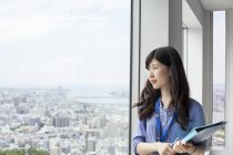Young businesswoman holding files and looking through window in office building. — Stock Photo