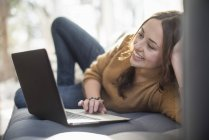 Cheerful young woman lying on sofa and using laptop. — Stock Photo