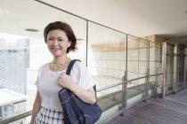 Молода жінка, прогулянки з сумочки доріжки в Офісна будівля. — стокове фото