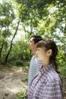 Side view of couple enjoying sunny weather in forest. — Stock Photo