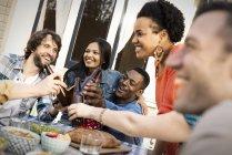 Grupo de homens e mulheres, reunindo em torno de uma refeição e bebidas tabela e tendo. — Fotografia de Stock