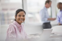 Young woman sitting at desk and using laptop in office with coworkers in background. — Stock Photo