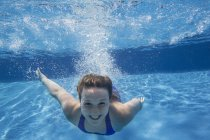 Cheerful pre-adolescent girl swimming underwater in pool. — Stock Photo