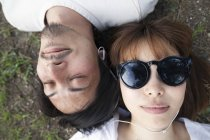 Overhead view of young Japanese man and woman in sunglasses lying on ground. — Stock Photo