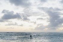 Man stand up paddling in calm water at dusk under scenic cloudscape. — Stock Photo