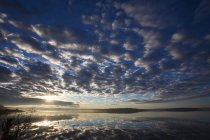 Padrão de nuvens dramáticas em todo o céu sobre a água do lago. — Fotografia de Stock