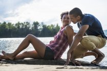 Пара сидящих вместе на пирсе у озера летом . — стоковое фото