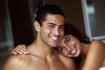 Молодий топлес чоловік і жінка, посміхаючись і обіймаються в приміщенні. — стокове фото