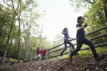 Elementary age children running around paddock with wooden fencing at country. — Stock Photo
