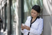 Бизнесмен в белой куртке проверяет телефон, опираясь на стену на улице . — стоковое фото