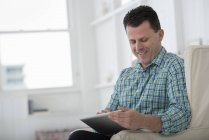 Mature man sitting in armchair and using digital tablet. — Stock Photo