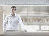 Мужчина в белой рубашке с открытым воротником в воздушном здании опирается на перила . — стоковое фото