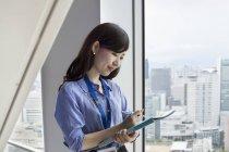 Junge Geschäftsfrau hält Akten in der Hand und blickt in Bürogebäude. — Stockfoto