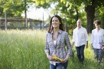 Reifes Paar und junge Frau mit Schutzhandschuhen gehen auf Bauernhof durch langes Gras. — Stockfoto