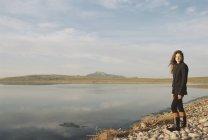 Середині дорослих жінку, що стоїть на скелястому березі озера — стокове фото
