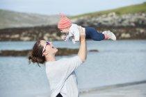 Mãe levantando bebê no ar à beira-mar . — Fotografia de Stock