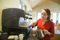 Young woman making coffee using large coffee machine. — Stock Photo