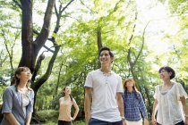 Group of Asian friends standing in sunny forest. — Stock Photo