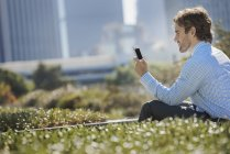 Young man sitting on park bench in city and using mobile phone. — Stock Photo