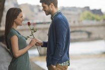 Mid adult man offering woman red rose on city street. — Stock Photo
