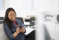 Mulher, verificando o smartphone na cadeira confortável no interior do escritório moderno — Fotografia de Stock