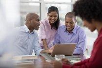Коллеги за столом и с помощью цифрового планшета и ноутбука . — стоковое фото
