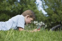 Elementary age boy lying on grass and playing handheld electronic game. — Stock Photo