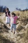 Zwei Kinder im Grundalter spielen in Sanddünen. — Stockfoto