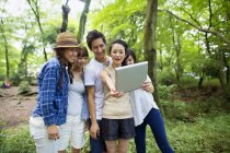 Group of Asian friends taking selfie with digital tablet in forest. — Stock Photo