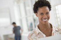 Mulher adulta média sorrindo e olhando na câmera no escritório . — Fotografia de Stock