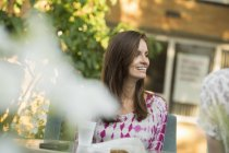 Cheerful woman sitting at table in garden. — Stock Photo