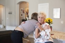 Teenage girl hugging senior woman in home interior. — Stock Photo