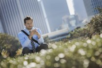 Young man sitting on park bench in city and using smartphone. — Stock Photo