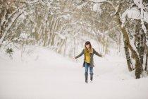 Mujer adulta media en nieve en el bosque. - foto de stock