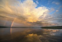 Веселка і формування драматичні хмари над озером води. — стокове фото