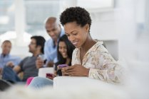 Mid adult woman checking smartphone with people having party in background. — Stock Photo