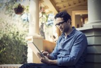 Man using digital tablet on porch on countryside house. — Stock Photo