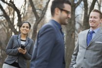 Empresários e empresária com smartphone relaxante no parque da cidade — Fotografia de Stock