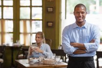 Male waiter standing with arms folded in cafe interior with woman holding coffee in background. — Stock Photo
